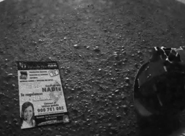 El folleto, en el suelo marciano después de haber sido arrancado del frontal de la cámara. Además, se aprecia la limpieza de la lente y se intuye el frescor a lavanda alrededor del robot.