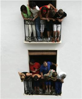 Vecinos esperando la llegada del furgón de reparto del supermercado para aprovisionarse desde los balcones.